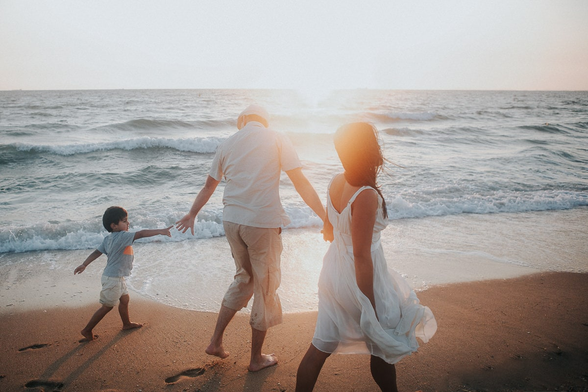 family walking along the beach at sunset - little boy reaching for hand of his dad - best family photographer in melbourne