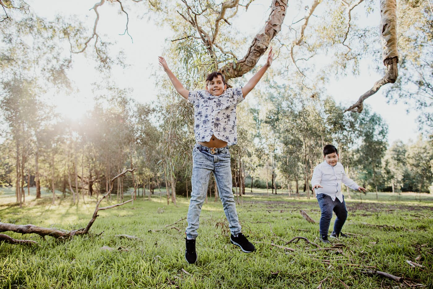 child jumping a starjump in forest - best nature family photography in Melbourne