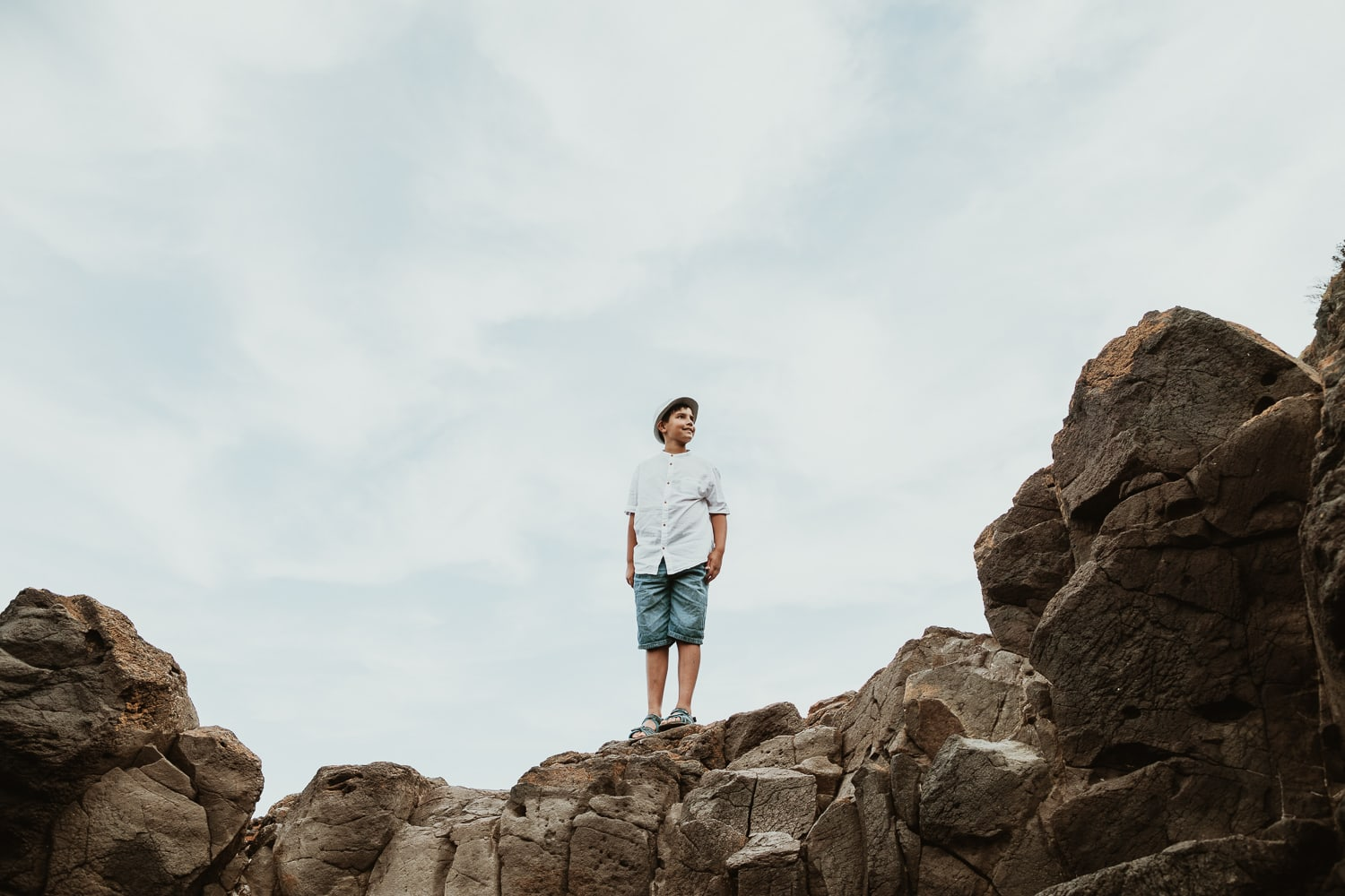 Mornington Peninsula - Kid on rocks looking to sky - wearing shorts and shirt - Cretive children and family photography