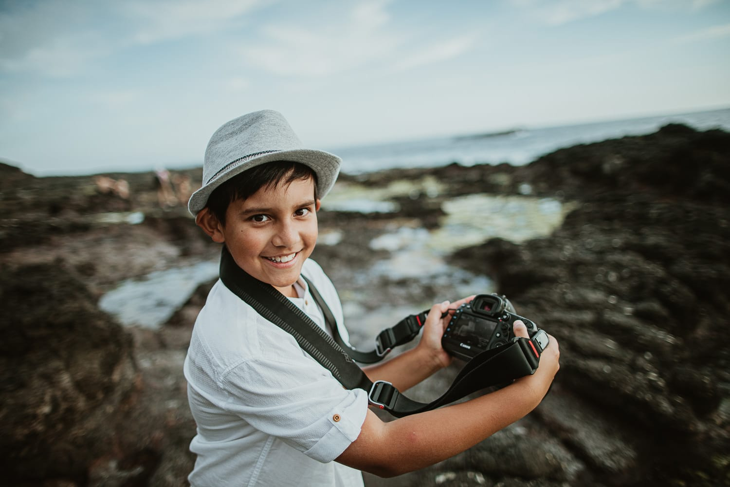 best photographer in melbourne - little boy holds professional Canon 5D IV camera and takes family photos