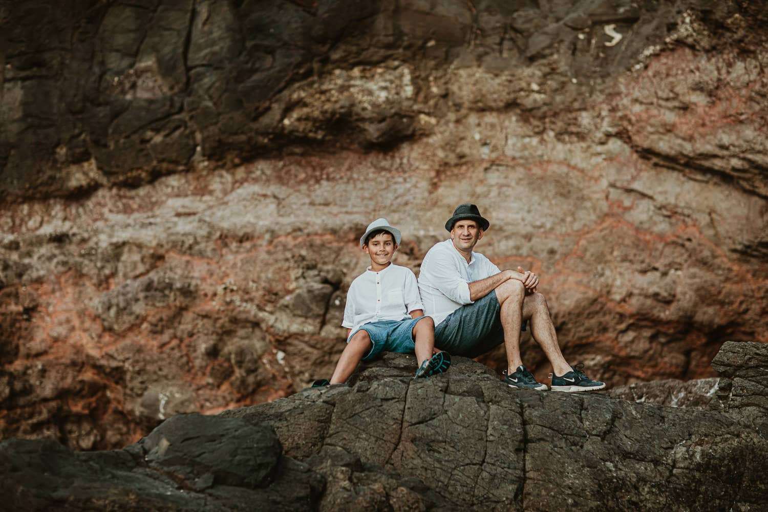 Dad and son sitting together on rocks in a family photoshoot session - Outdoor location photos